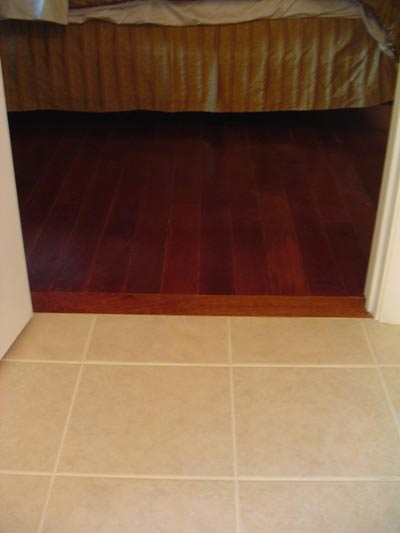 A flush transition between the hardwood and porcelain floors