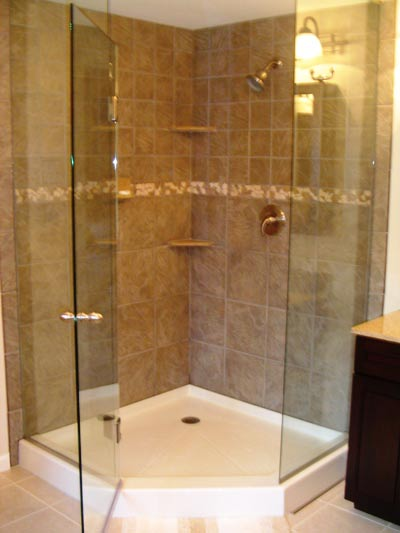 The oversized porcelain corner shower complete with a natural stone border and tumbled marble shelves and soap dish