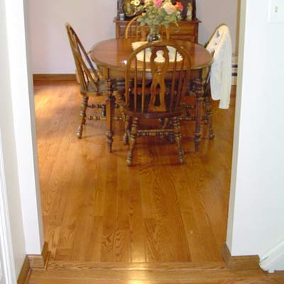 Hardwood Foyer transitioned into hardwood dining room with a direction change in in the boards, stain matched base molding