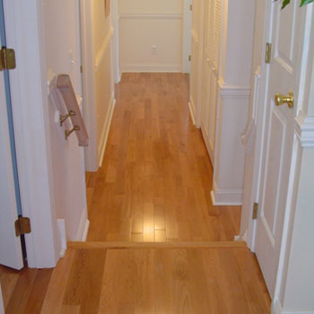 Boards run vertical to accentuate the hallway, contrasted with a tall white base trim and quarter round